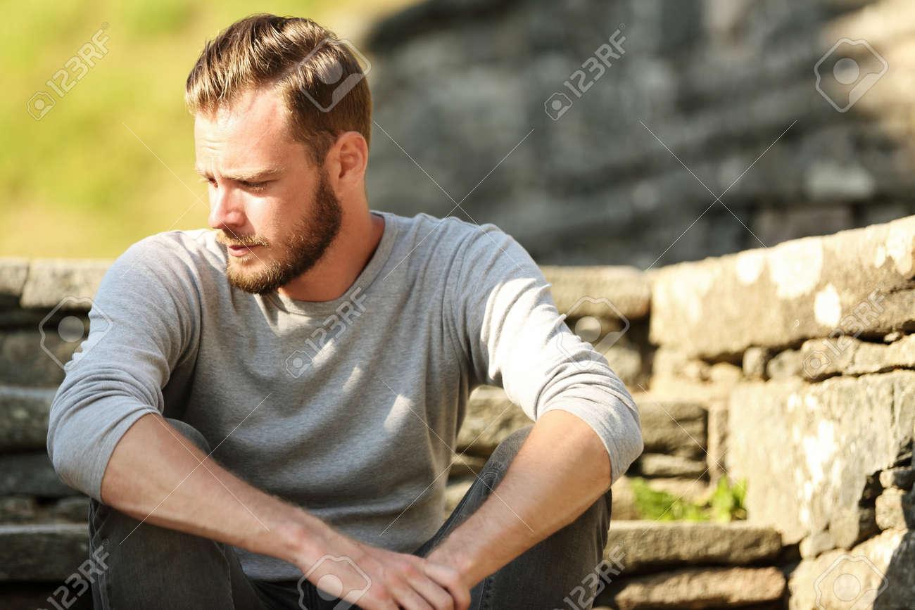 El Hombre De Unos 20 Anos Con Una Camisa Gris Y Pantalones Vaqueros Sentado Afuera En Un Conjunto De Pasos En Un Dia Soleado De Verano Fotos Retratos Imagenes Y Fotografia De