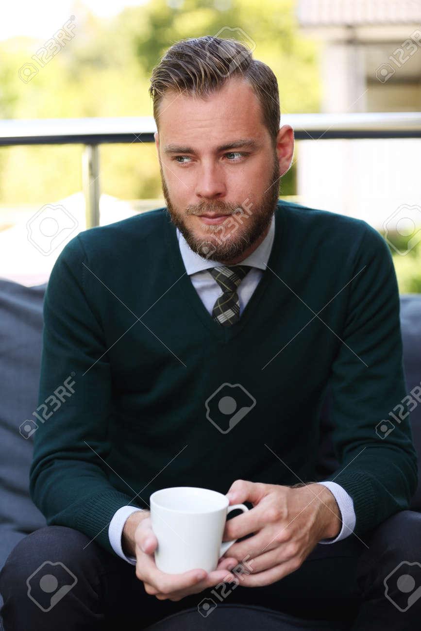 Un Bel Homme Dans Une Chemise Une Cravate Et Un Pull Assis A L