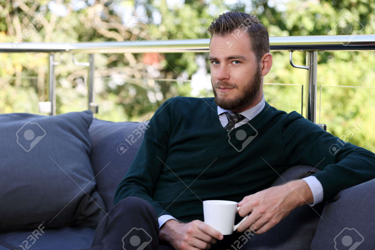 A Handsome Man In A Shirt Tie And Sweater Sitting Down Outside