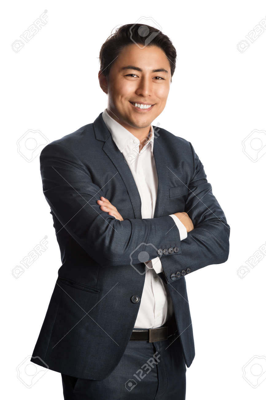 A well dressed businessman in a blue suit and white shirt, standing against a white background smiling towards camera. - 136716261
