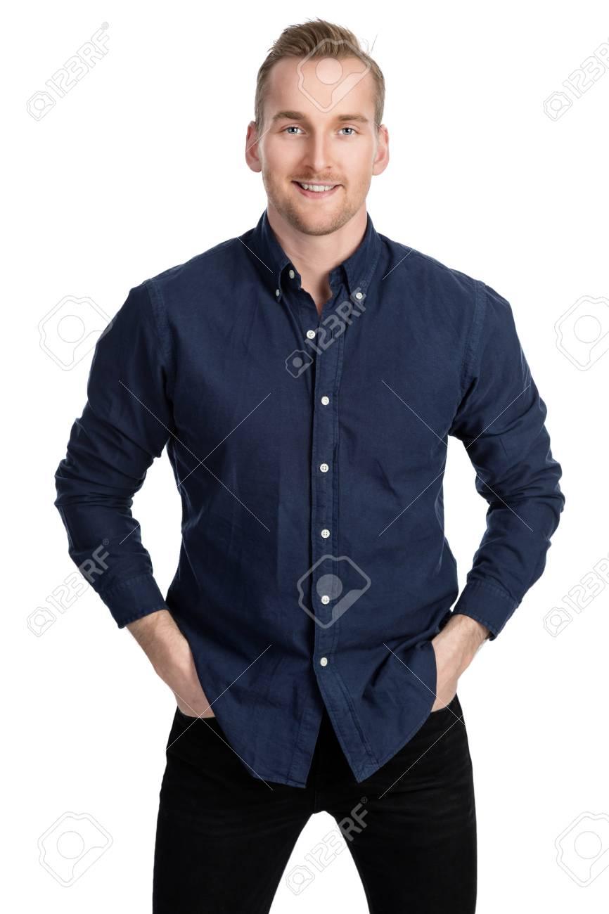 f091aa0a2c Uomo bionda bello che sta contro una priorità bassa bianca che porta una  camicia blu e dei jeans.