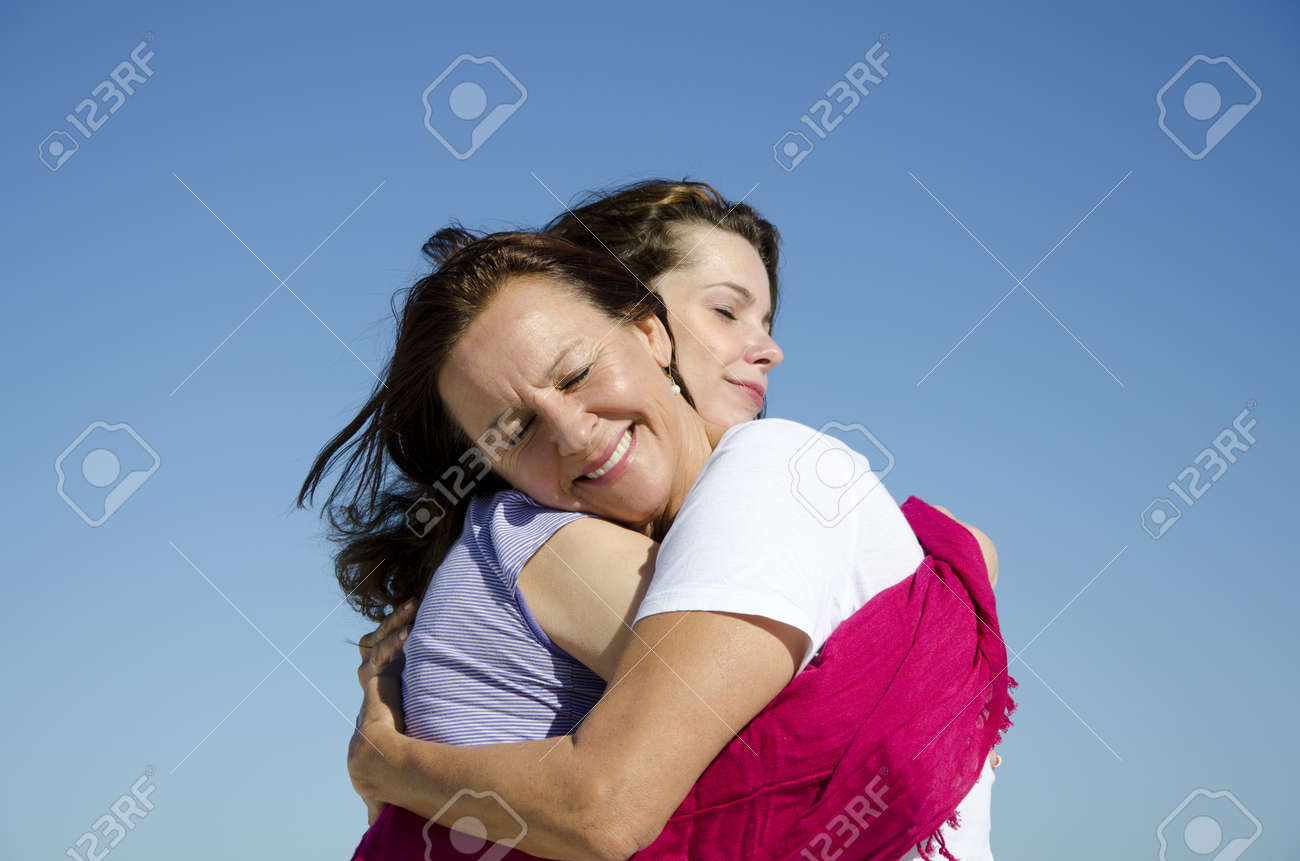 Feeling good, feeling happy: two women, two generations, mother and daughter holding each other in a cuddle, with clear blue sky as background and copy space. Stock Photo - 14213278
