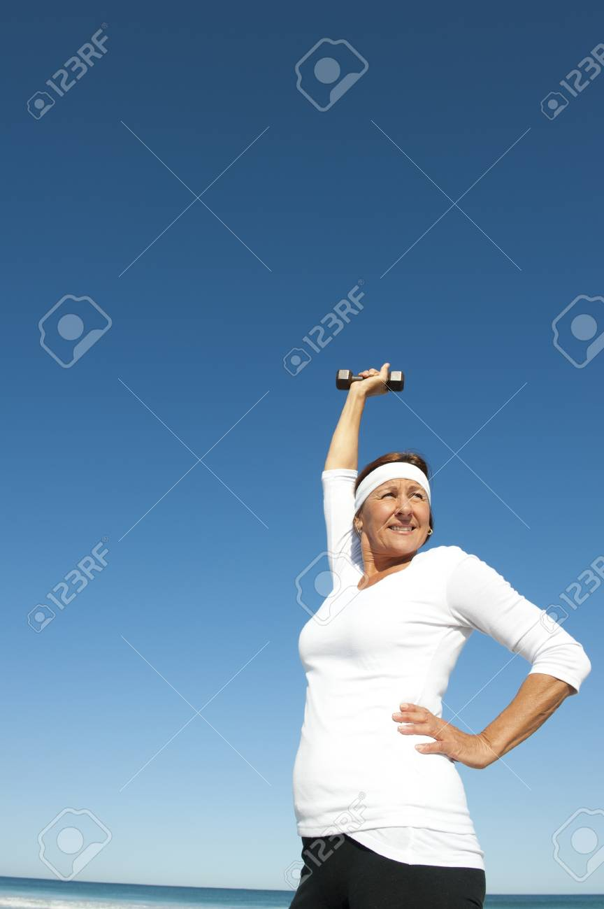 Attractive and active senior woman exercising with weights at the beach, with ocean and blue sky as background and copy space. Stock Photo - 15376584