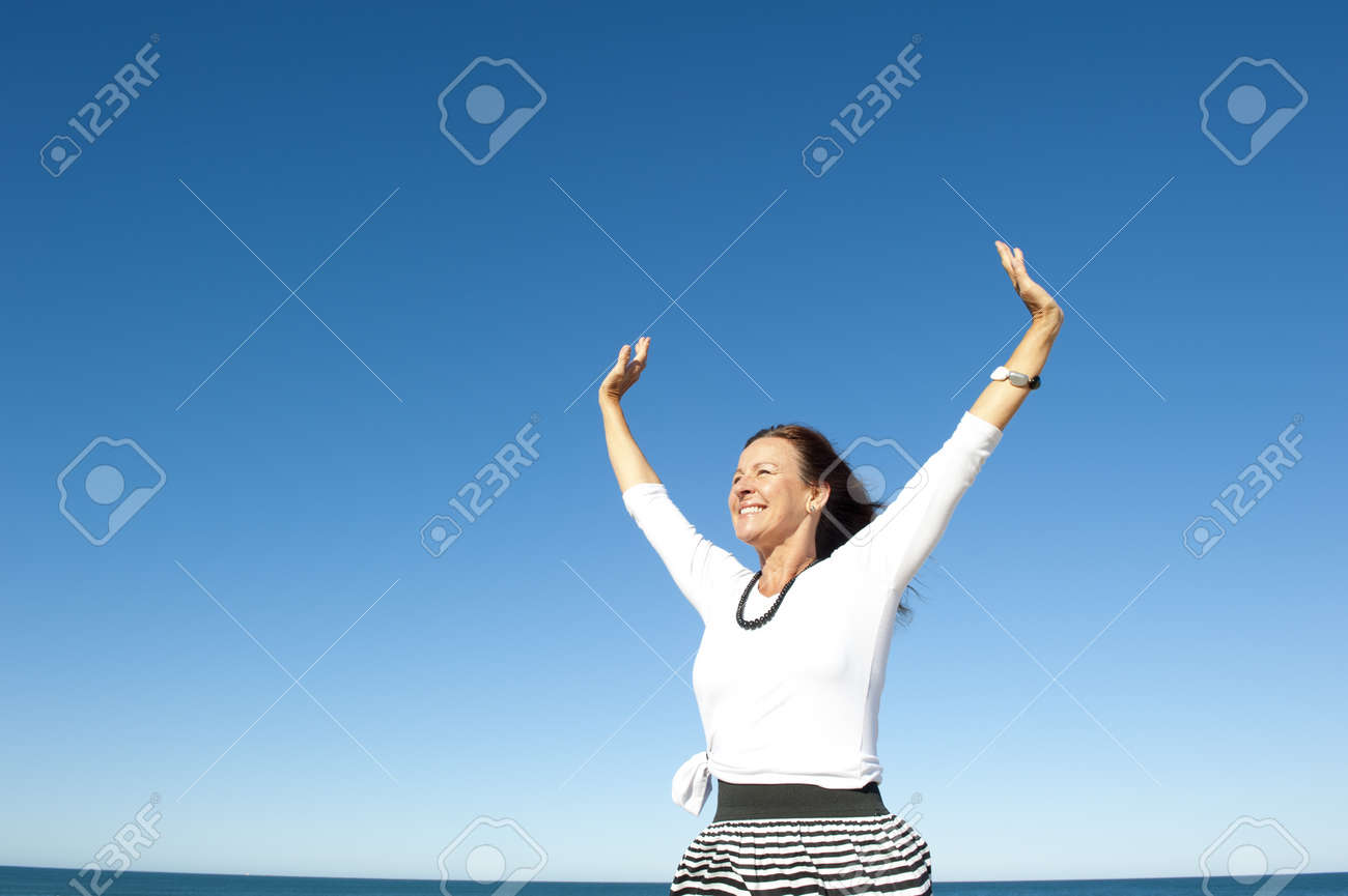 Attractive and successful looking mature woman cheerful and happy with arms up, isolated with blue sky as background and copy space Stock Photo - 15377937