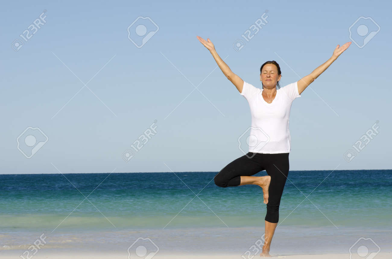 Attractive and active senior woman keeping fit and healthy with stretching pilates exercises at beach, with ocean and blue sky as background and copy space. Stock Photo - 15400692