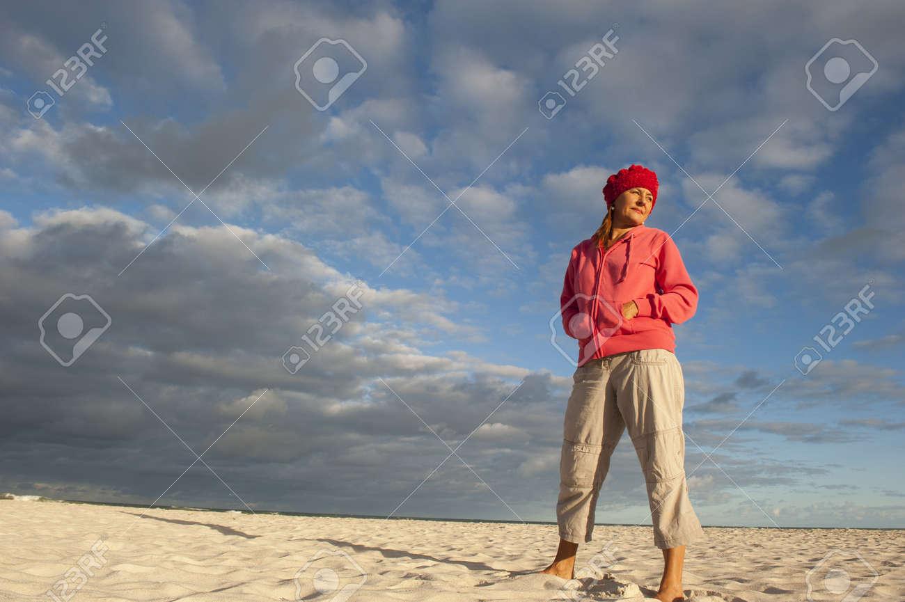 enfant nouveaux produits pour Pré-commander Portrait d'une femme d'être belle âgé debout pose occasionnelle sur la  plage, le port de pull rose et bonnet rouge, avec lumière solaire doux sur  son ...