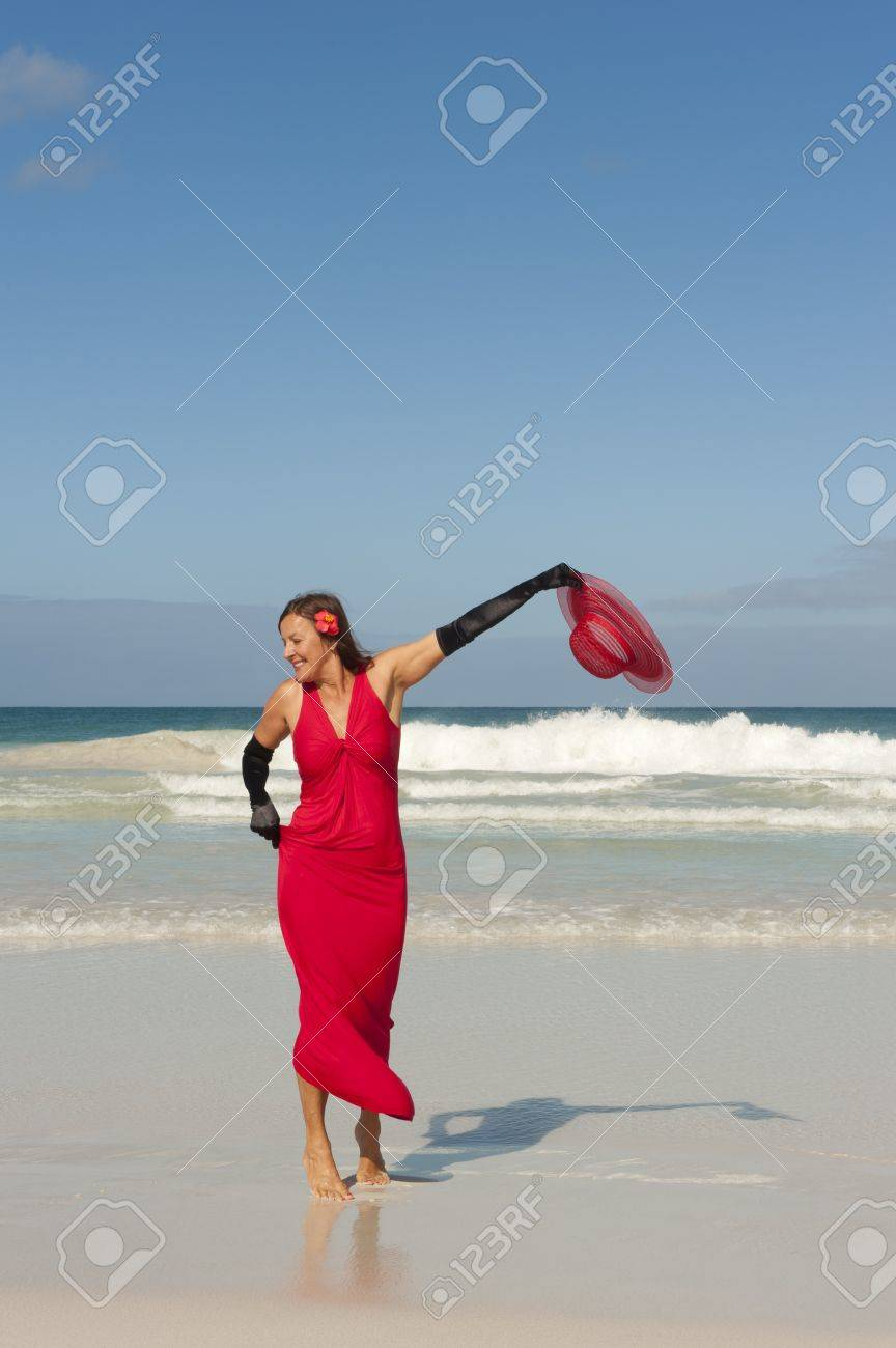 Sexy looking lady posing happy smiling in elegant red dress and long black gloves dancing at beach, isolated with ocean and blue sky as background and copy space. Stock Photo - 16409984