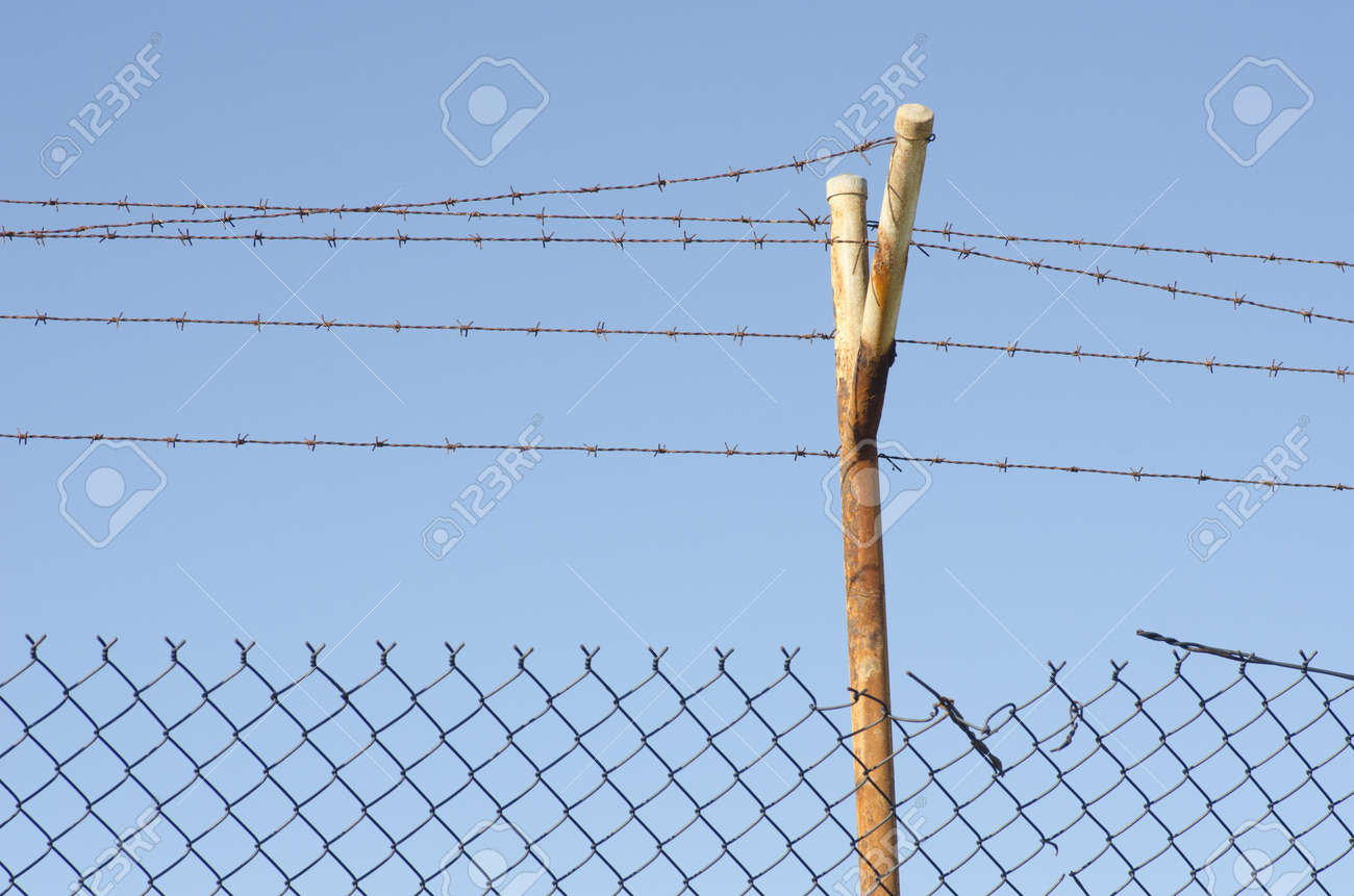 Barb wire fence and rusty metal pole with blue sky as background and copy space. Stock Photo - 16785484