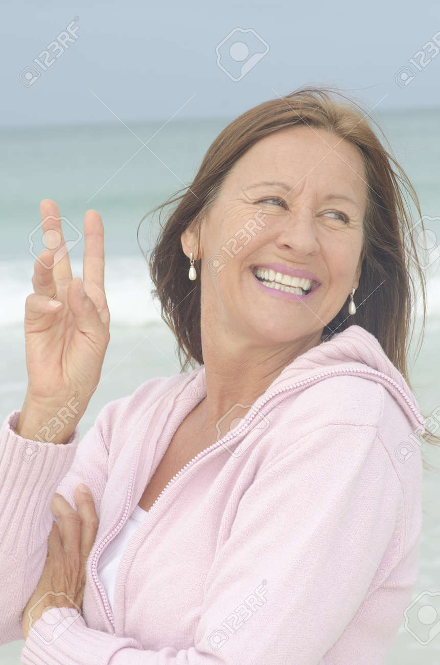 Portrait attractive middle aged woman enjoying active retirement, happy smiling, isolated with ocean as blurred background. Stock Photo - 16880809