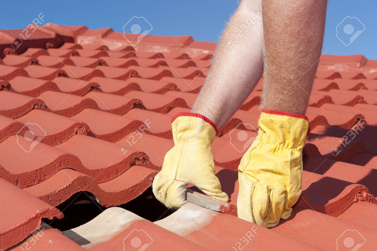 Roof repair, worker with yellow gloves replacing red tiles or shingles on house with blue sky as background and copy space Stock Photo - 17644125