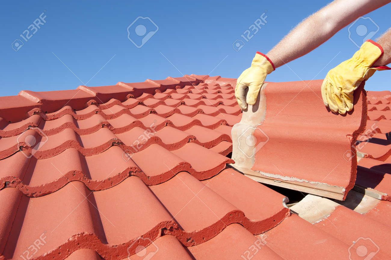 Roof repair, worker with yellow gloves replacing red tiles or shingles on house with blue sky as background and copy space. Stock Photo - 17644195