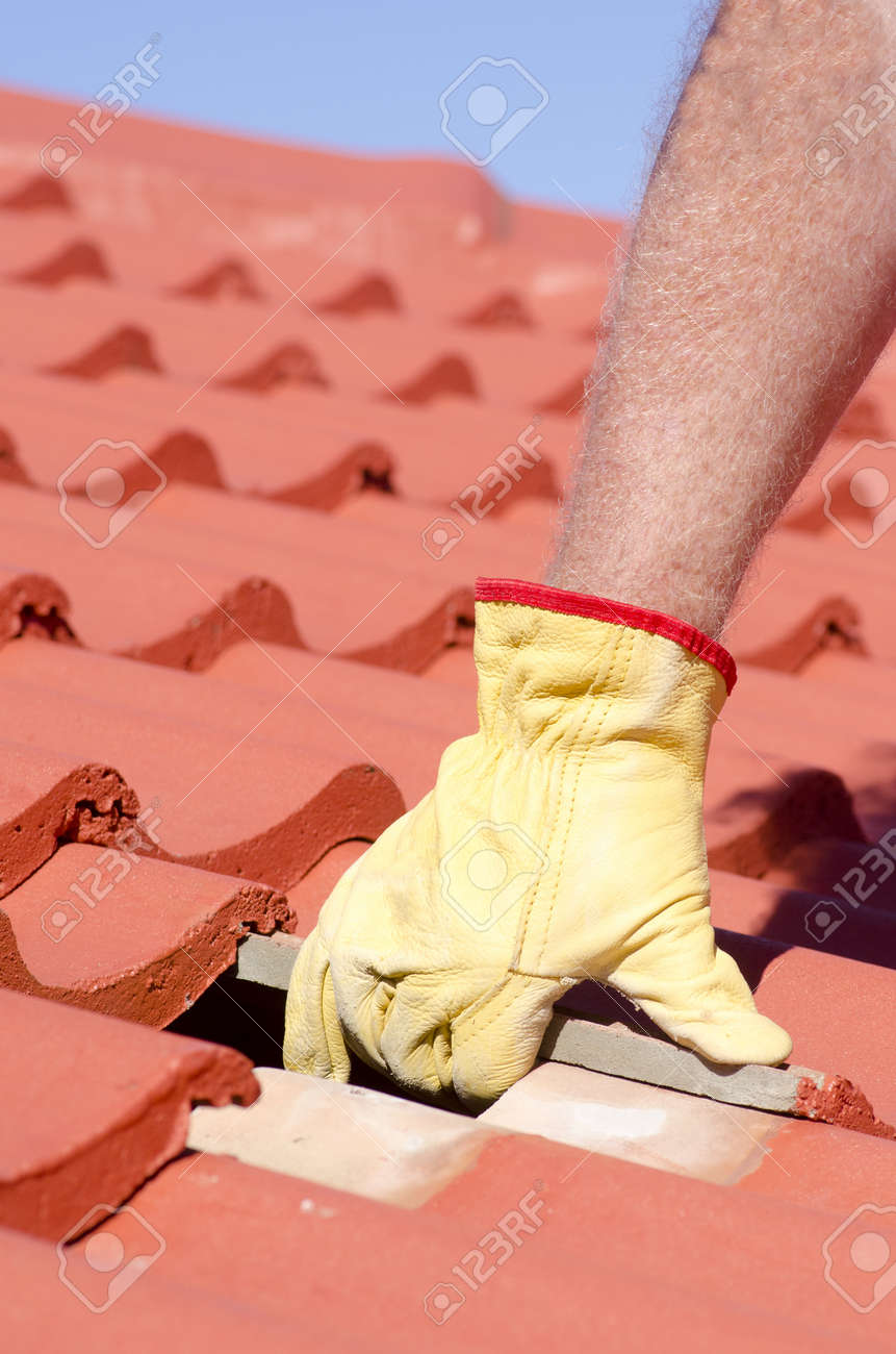 Roof repair, worker with yellow gloves replacing red tiles or shingles on house with blue sky as background and copy space. Stock Photo - 17644249