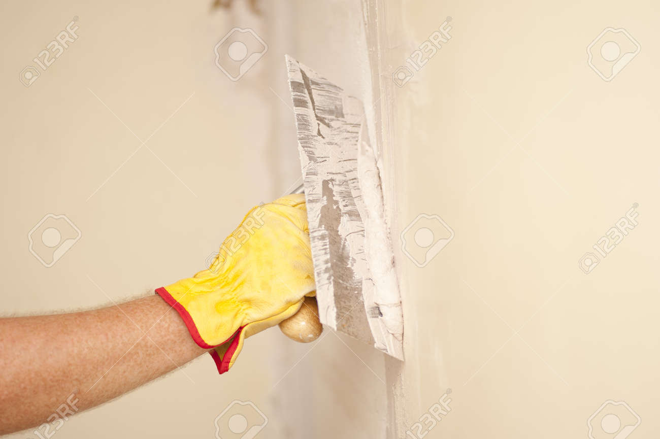 Closeup of palette-knife or scraper and cement filling for house renovation construction in hands of handyman and worker fixing interior wall, with blurred background and copy space. Stock Photo - 18457921