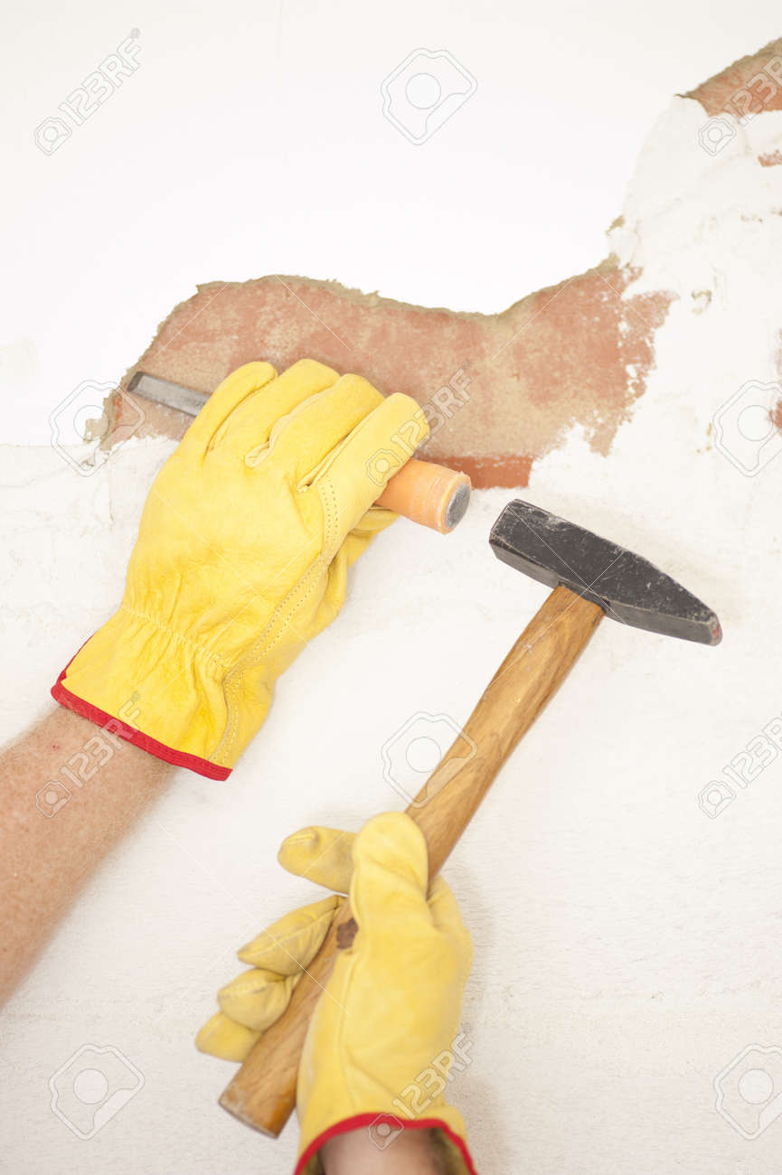 Workers hands with yellow gloves repairing, renovating interior wall in house with hammer and bite or chisel or gouge. Stock Photo - 18457930