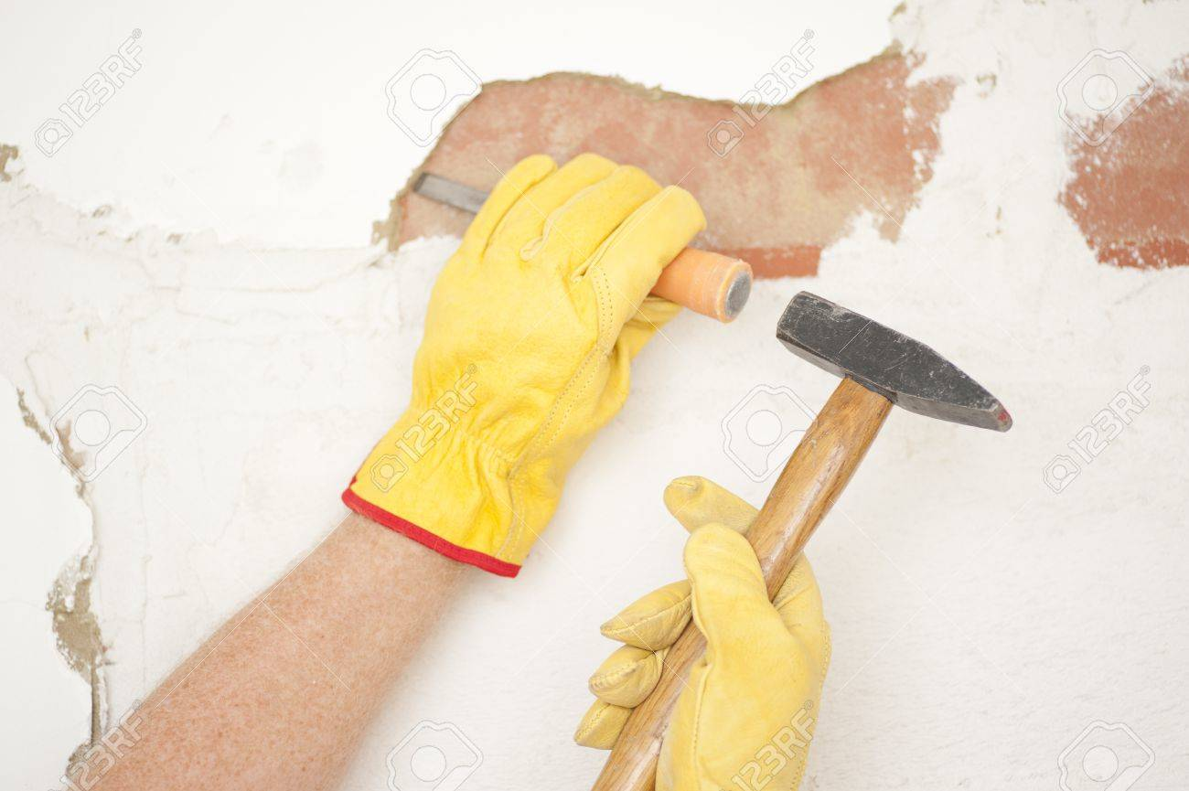 Workers hands with yellow gloves repairing, renovating interior wall in house with hammer and bite or chisel or gouge. Stock Photo - 18457927