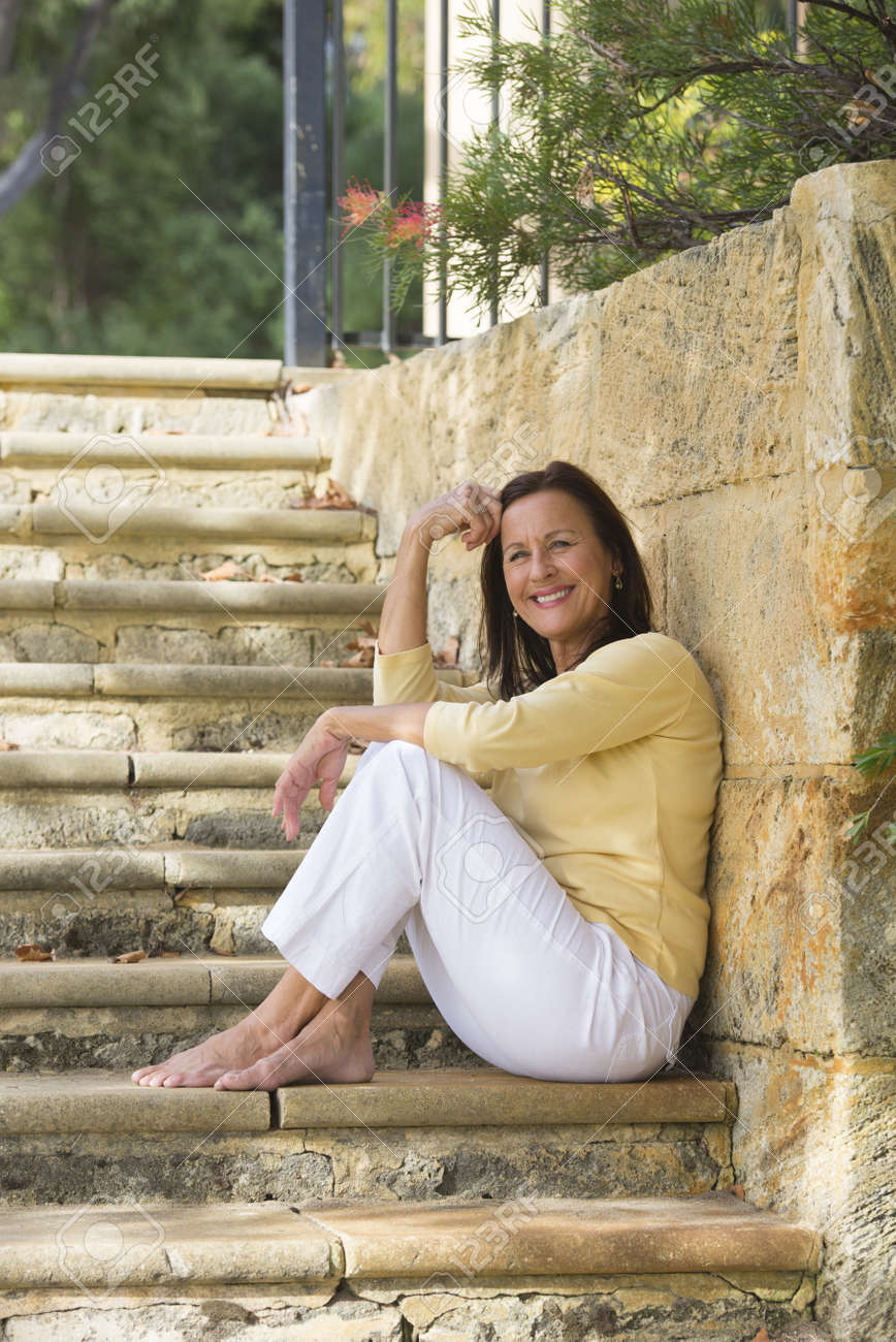 portrait confident beautiful mature woman sitting relaxed and happy