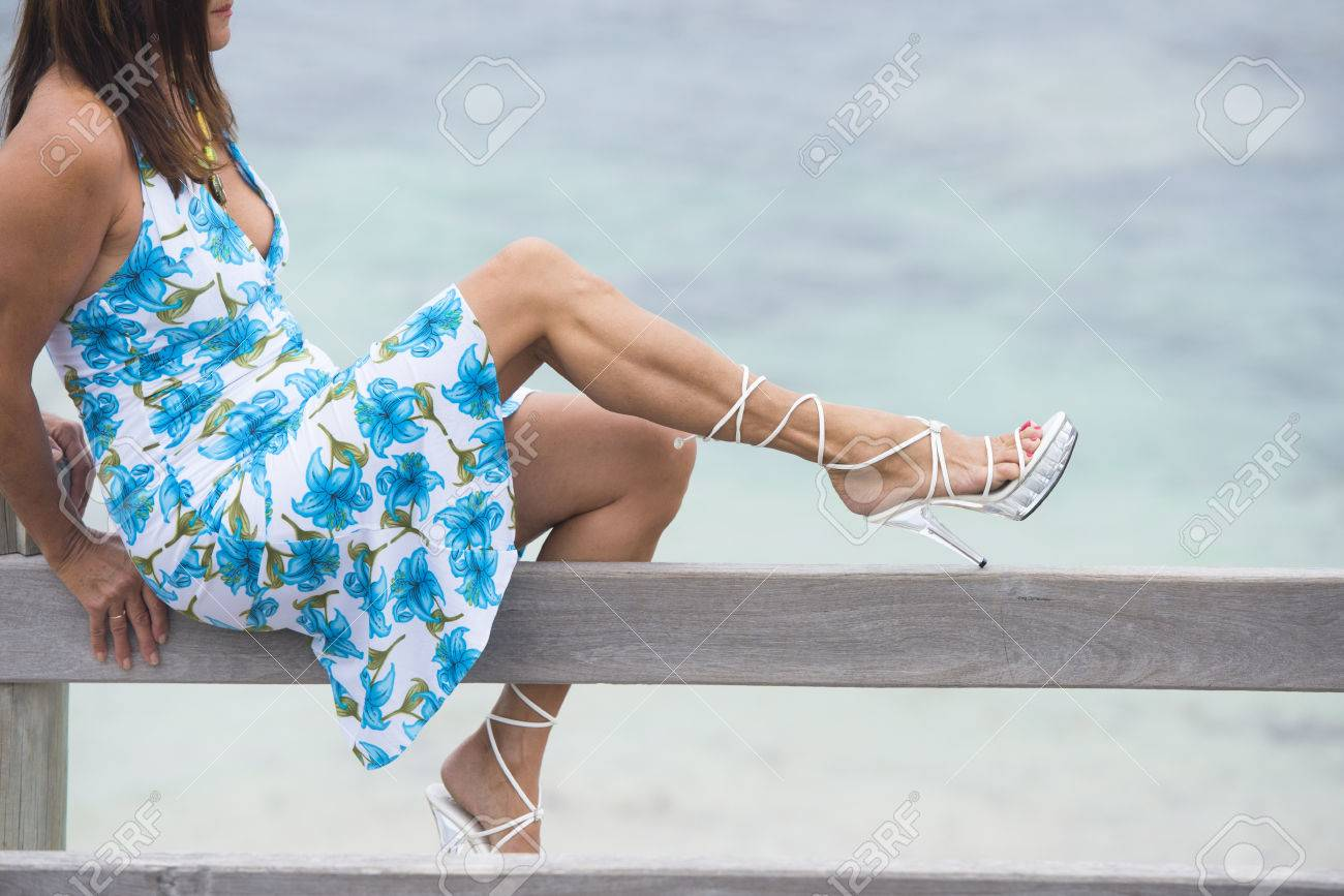 Portrait attractive mature woman sitting on wooden handrail, wearing summer  dress and high heel shoes - Portrait Attractive Mature Woman Sitting On Wooden Handrail