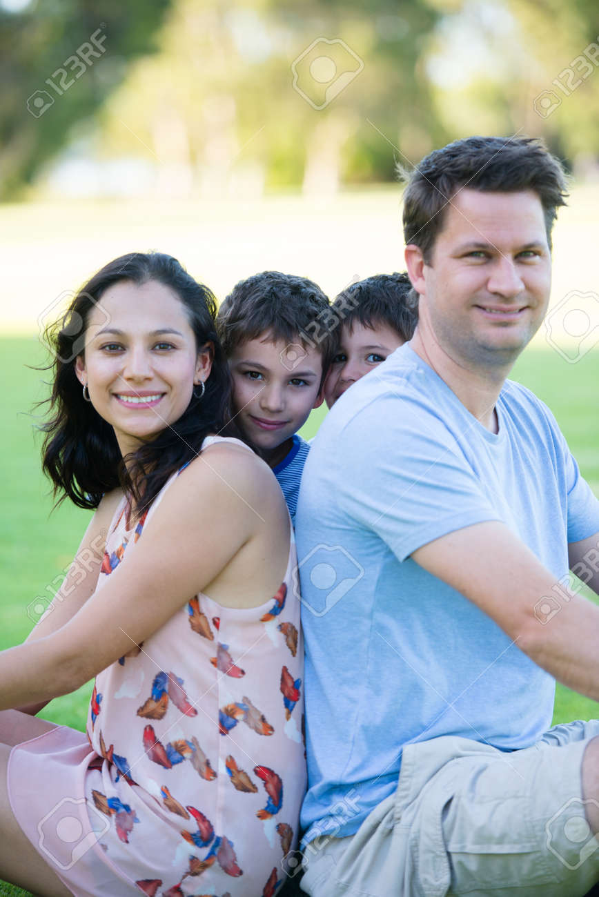 Portrait happy relaxed interracial family in park outdoors, with young sons  peeking, looking,