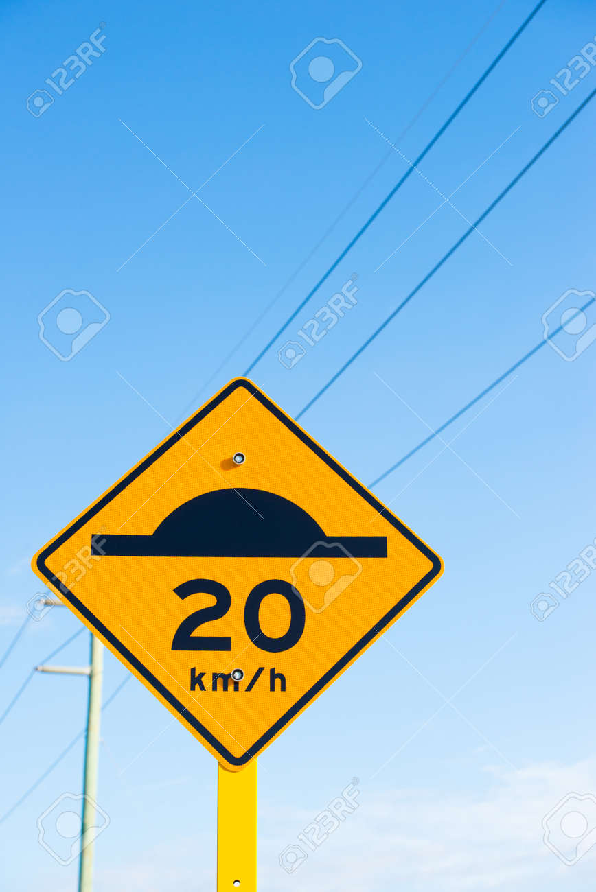 Street sign with speed bump icon black on yellow and slow down