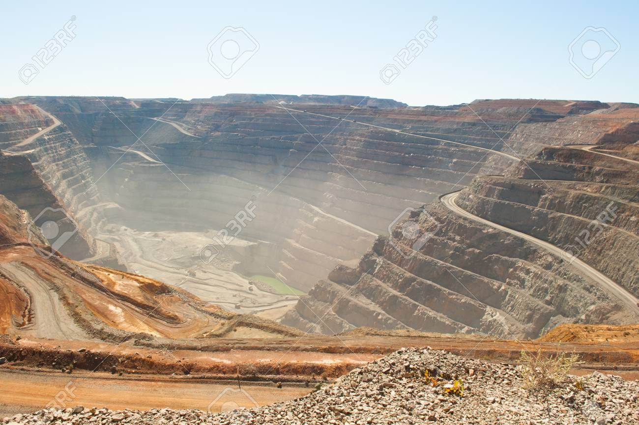 Panoramic aerial view of Super Pit goldmine in Kalgoorlie, Western Australia, with winding path along edges of the whole, heavy machinery, copy space - 80077113