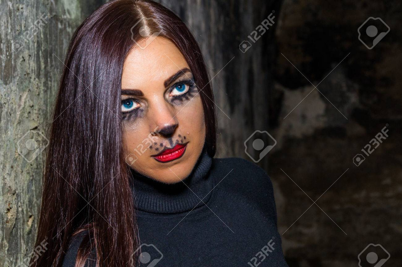 Sexy woman with a cat face makeup in an old fort. Stock Photo - 65781428