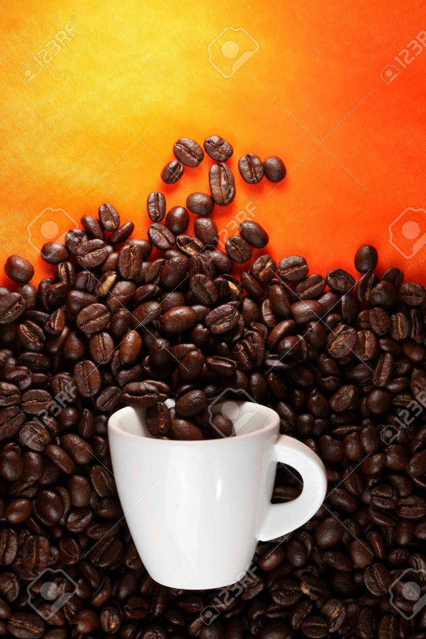 Coffee cup with beans on orange background. Stock Photo - 11819944