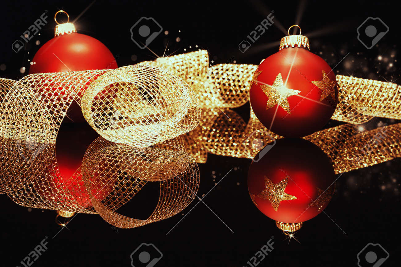 red christmas balls with glitter stars with golden metal ribbon on a black mirror Stock Photo - 14932315