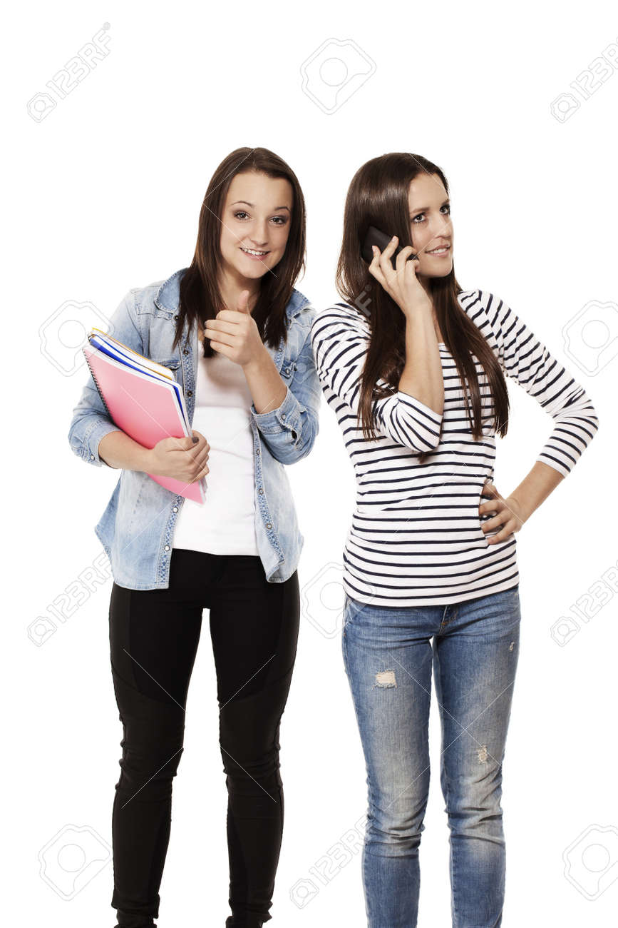 teenage student showing thumb up while her frind is on the phone on white background Stock Photo - 15177709