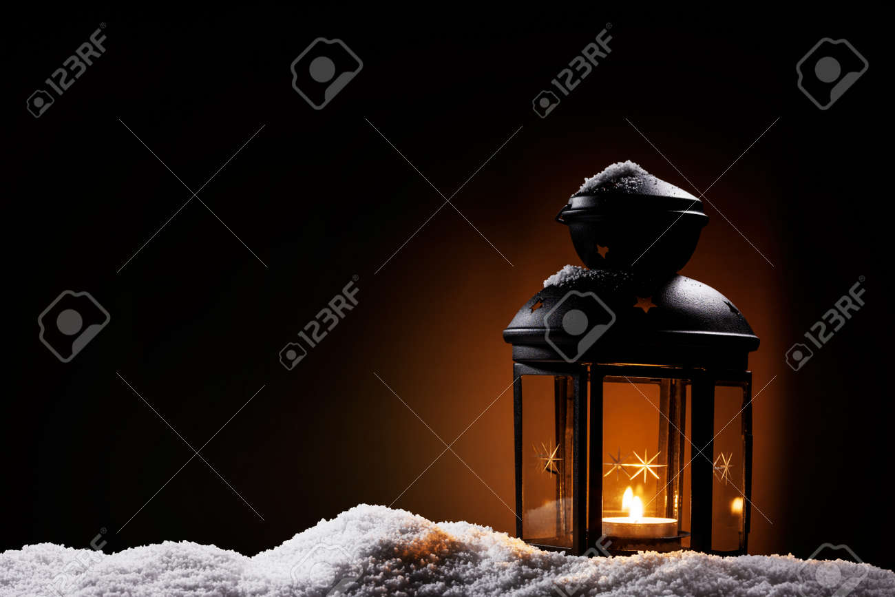 burning black vintage christmas lantern in the night on snow Stock Photo - 15220570
