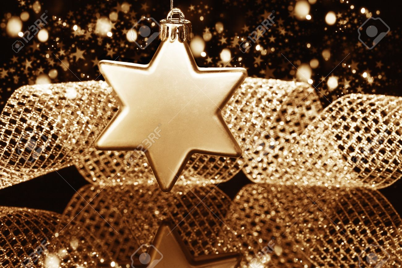 christmas ball in star shape in front of a metal ribbon and sparkling golden black background Stock Photo - 15220586
