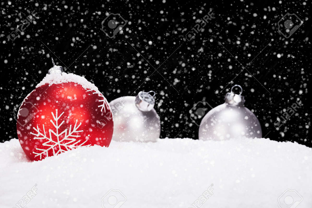 Red And Silver Christmas Balls In Snow On Black Background While ...