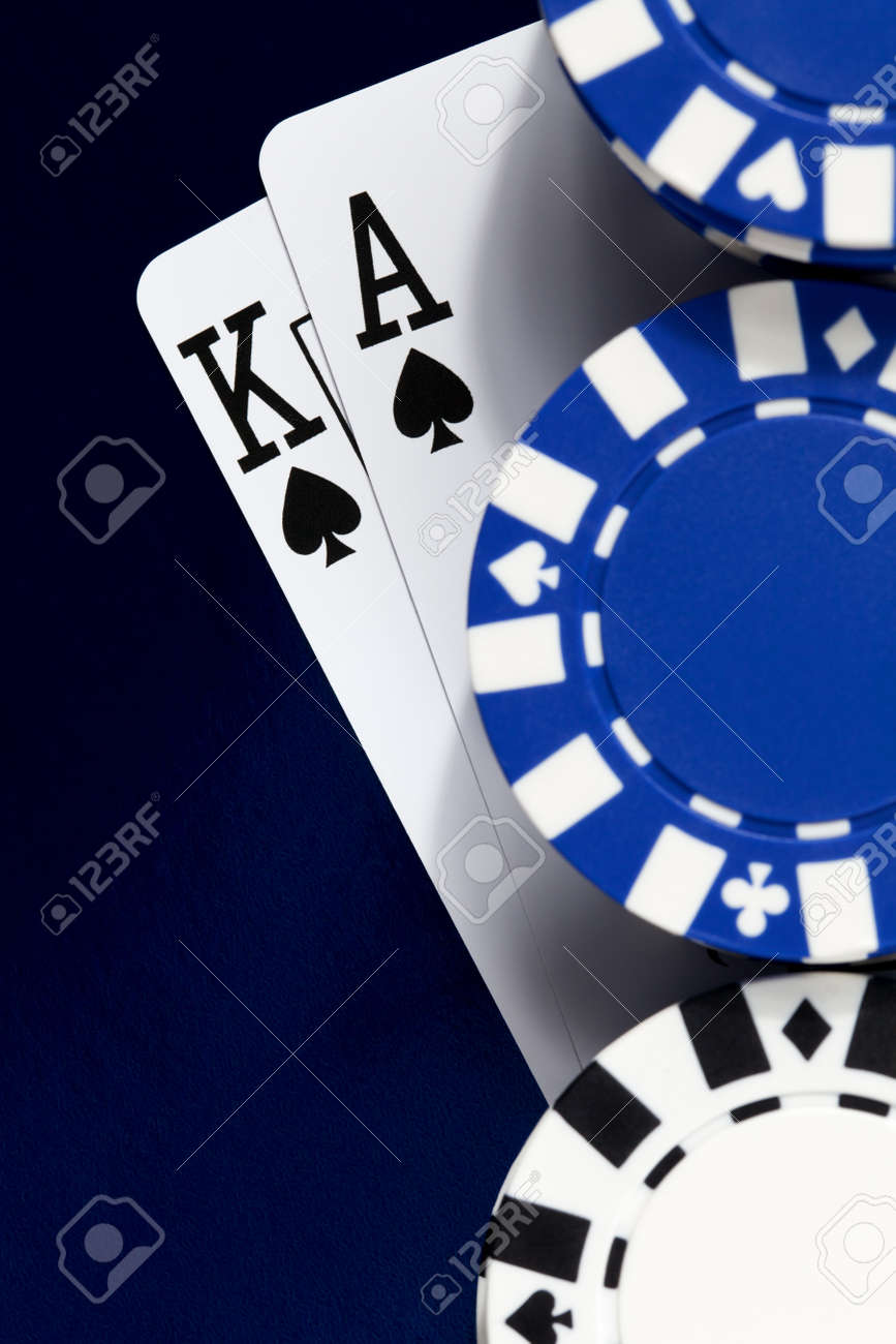 A king and ace of spades under a pile of poker chips on a shiny blue background. Stock Photo - 17308970