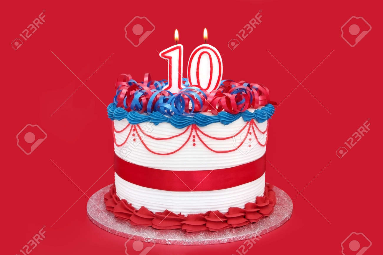 Cake With Number 10 Candles On Vibrant Red Background Stock Photo