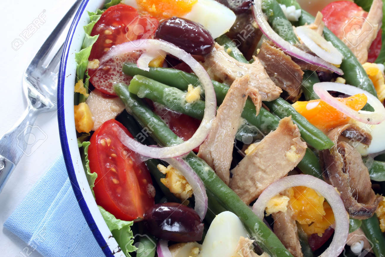 Salad Nicoise.  Tuna salad with green beans, eggs, chat potatoes, black olives, red onion, cherry tomatoes, anchovies, and a vinaigrette mustard dressing.  Delicious! Stock Photo - 2533586