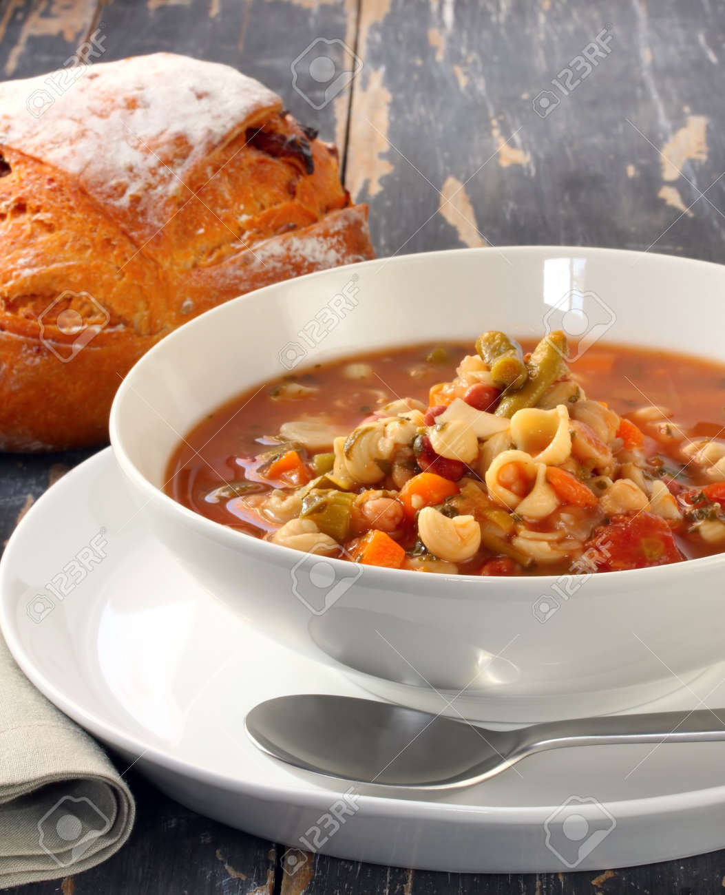 Minestrone pasta soup on rustic table, with fresh-baked cob of bread. Standard-Bild - 3161774
