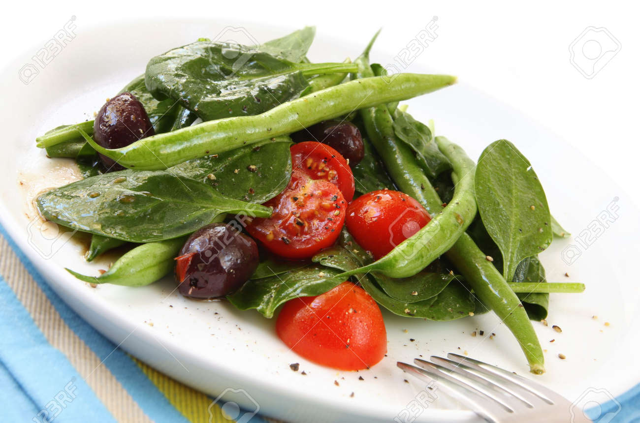 sald of spinach leaves chery tomatoes green beans and black