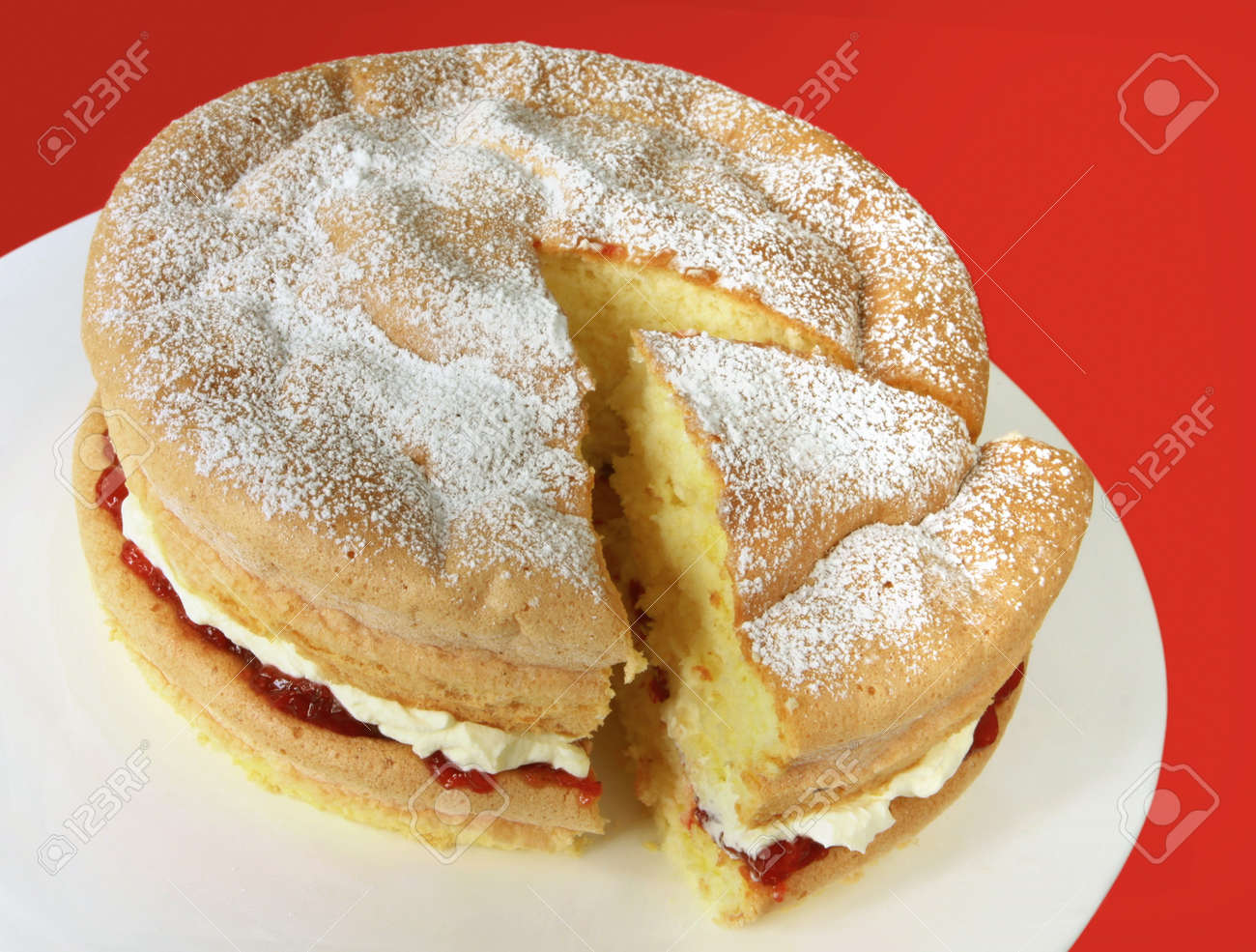 Home-baked sponge cake filled with fresh whipped cream and strawberry jam, and topped with powdered sugar. Stock Photo - 4467079