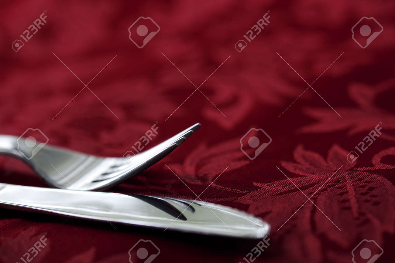 Silver knife and fork on red damask linen tablecloth.  Focus on fork tines. Stock Photo - 6789273