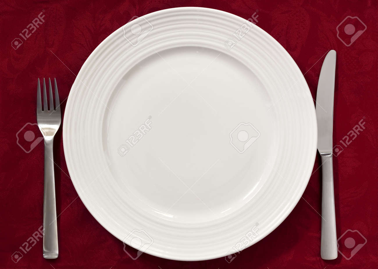 Dinner Setting place setting on red damask tablecloth. silverware and dinner