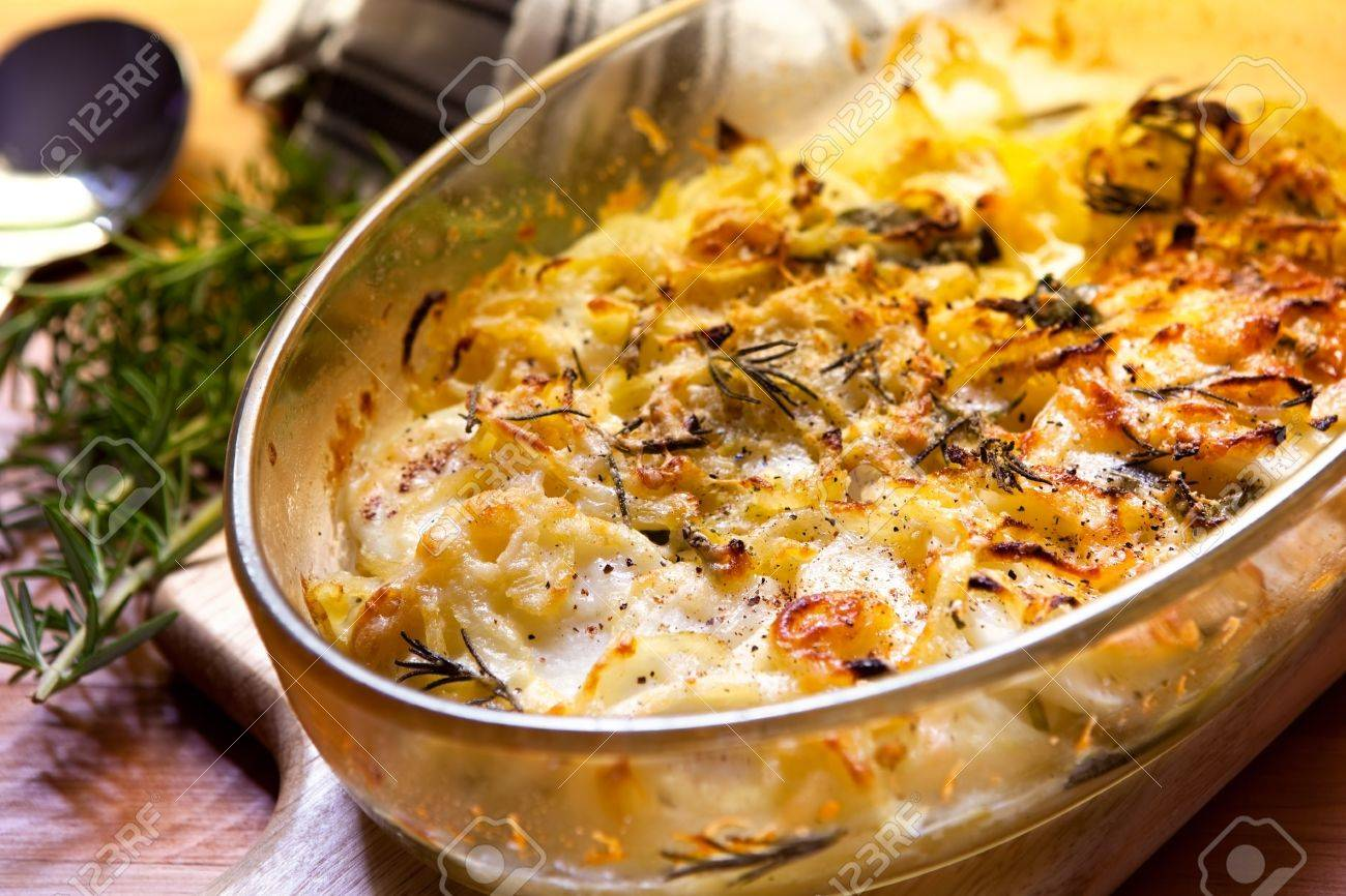 Potato and onion gratin with rosemary, in warm light. Stock Photo - 8180526