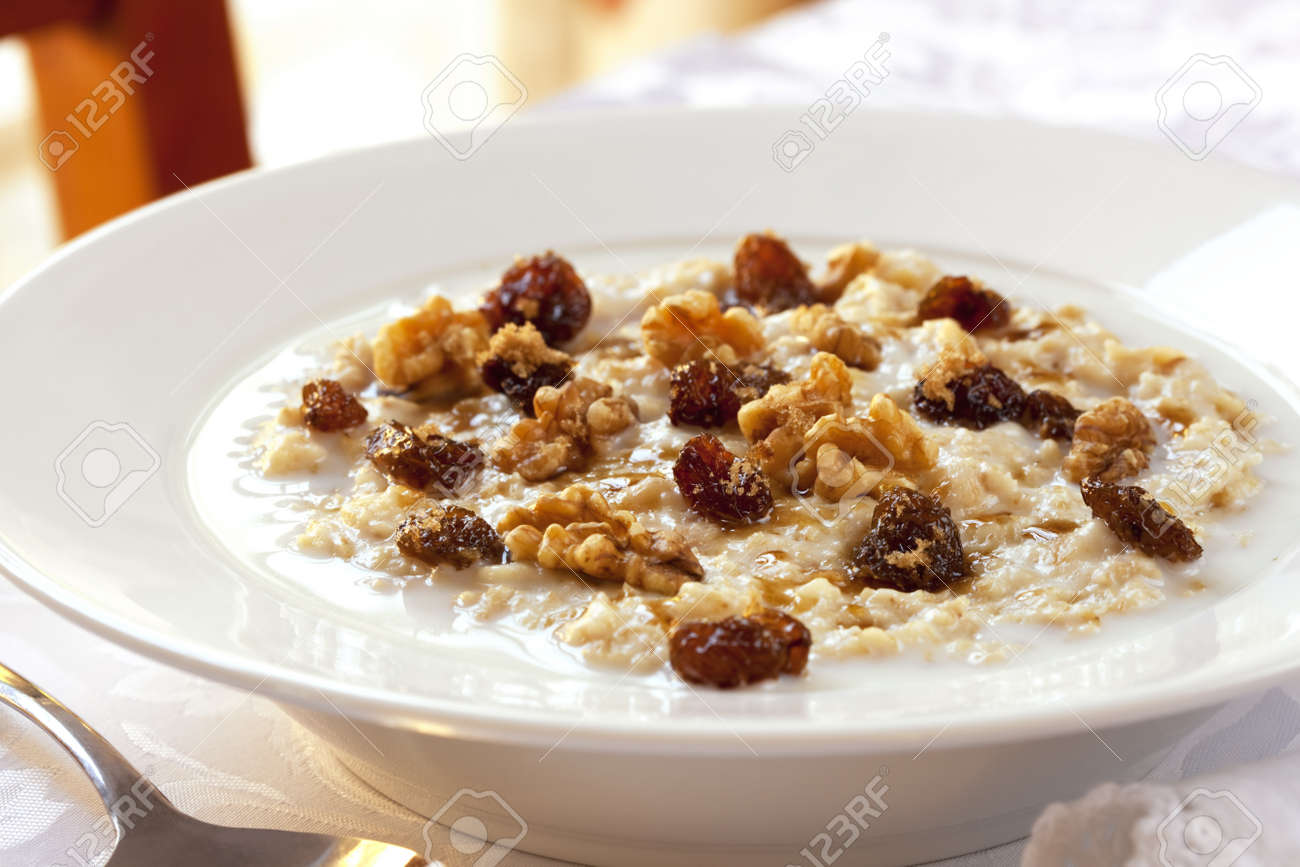 Bowl of oatmeal topped with raisins, walnuts and brown sugar.  Healthy eating. Stock Photo - 9674004