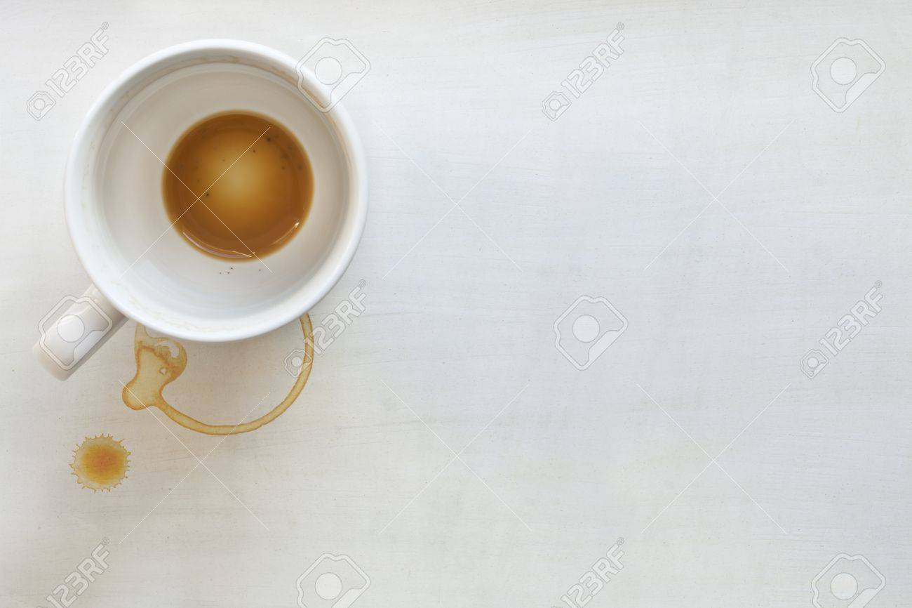 Coffee cup over white painted background.  Dregs in the bottom of the cup, with stains.  Lots of copyspace. Stock Photo - 9887870