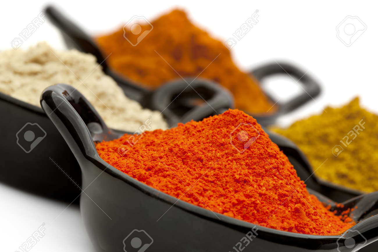 Variety of spices in small black bowls.  Focus on front bowl.  Includes saffron, ginger, and curry powders. Stock Photo - 9887648