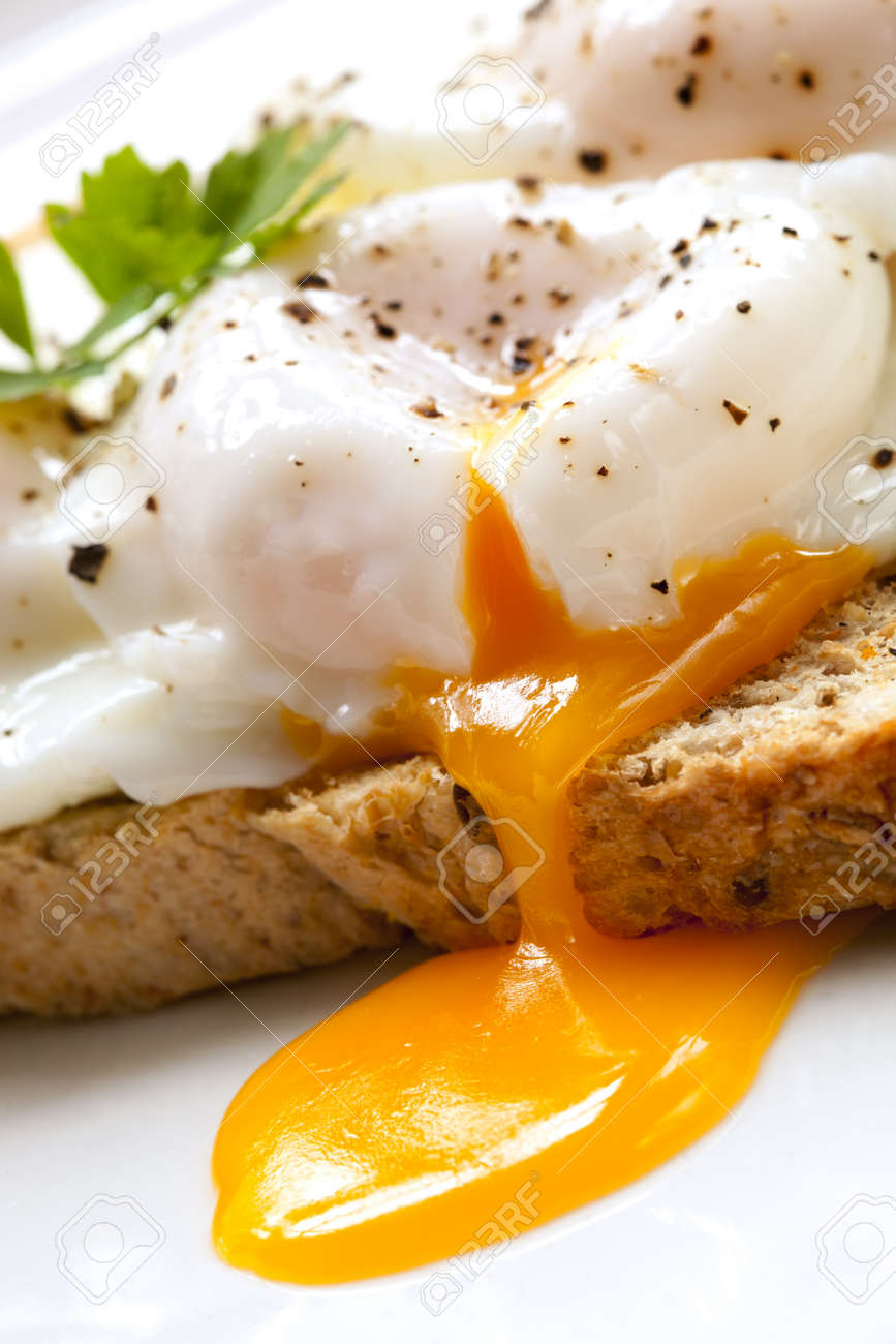Poached eggs on toast, garnished with parsley - 15871084