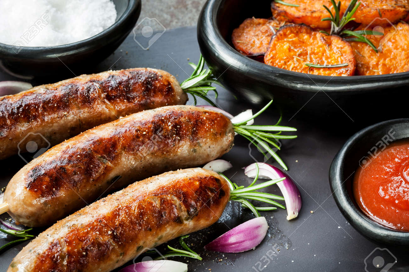 Grilled sausages with rosemary, sweet potato fries, and red onion. - 31418437