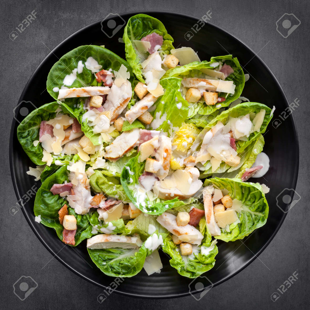 Chicken Caesar salad on black plate over slate. Overhead view. - 32575746