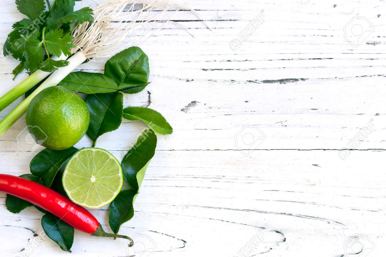 Kaffir lime leaves, fruit, coriander or cilantro, red chilli and green onions over white distressed wooden background. Overhead view. - 39647806