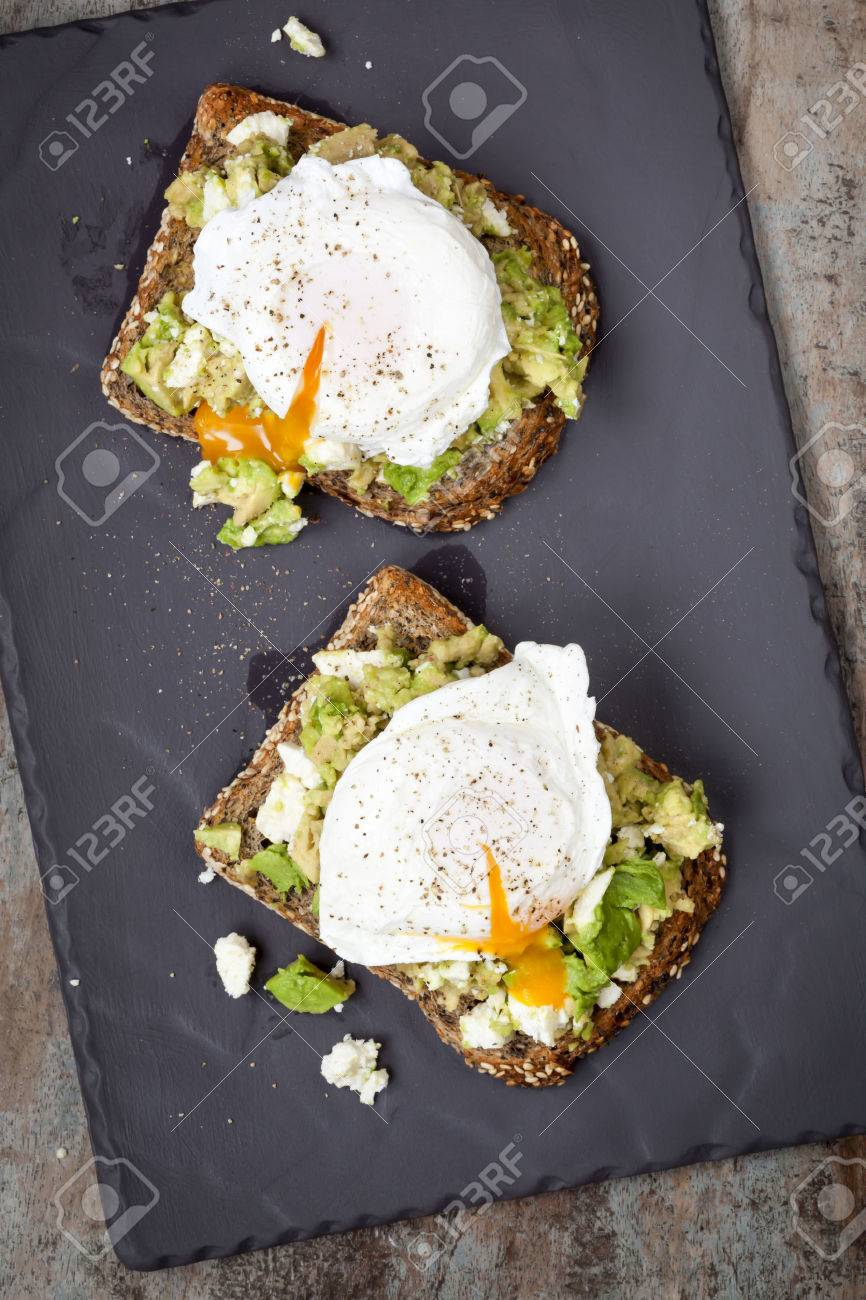 Smashed avocado and feta cheese toast with poached eggs. Overhead view, on dark slate. - 43880424