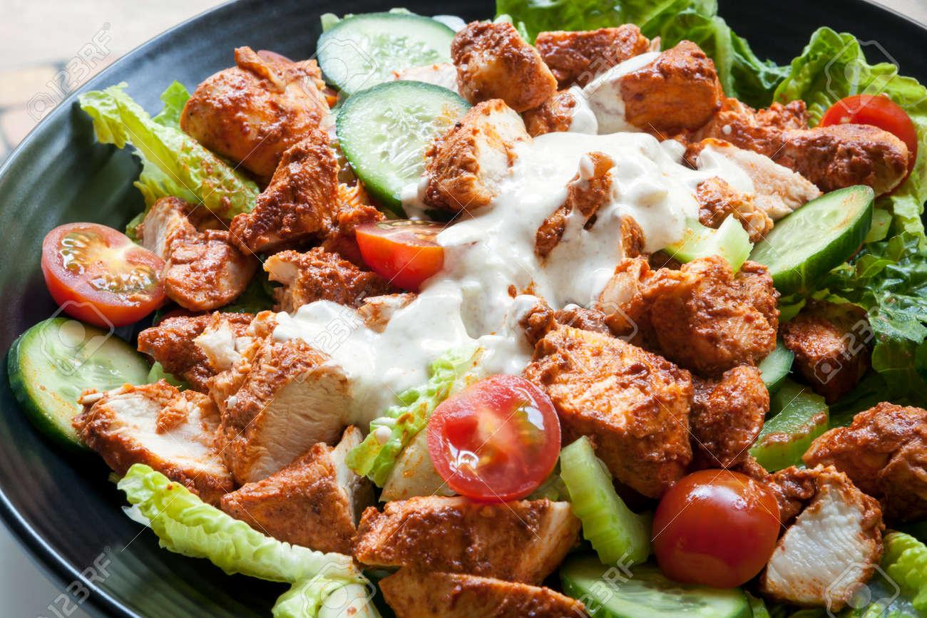 Tantoori chicken salad on black plate. - 50838886