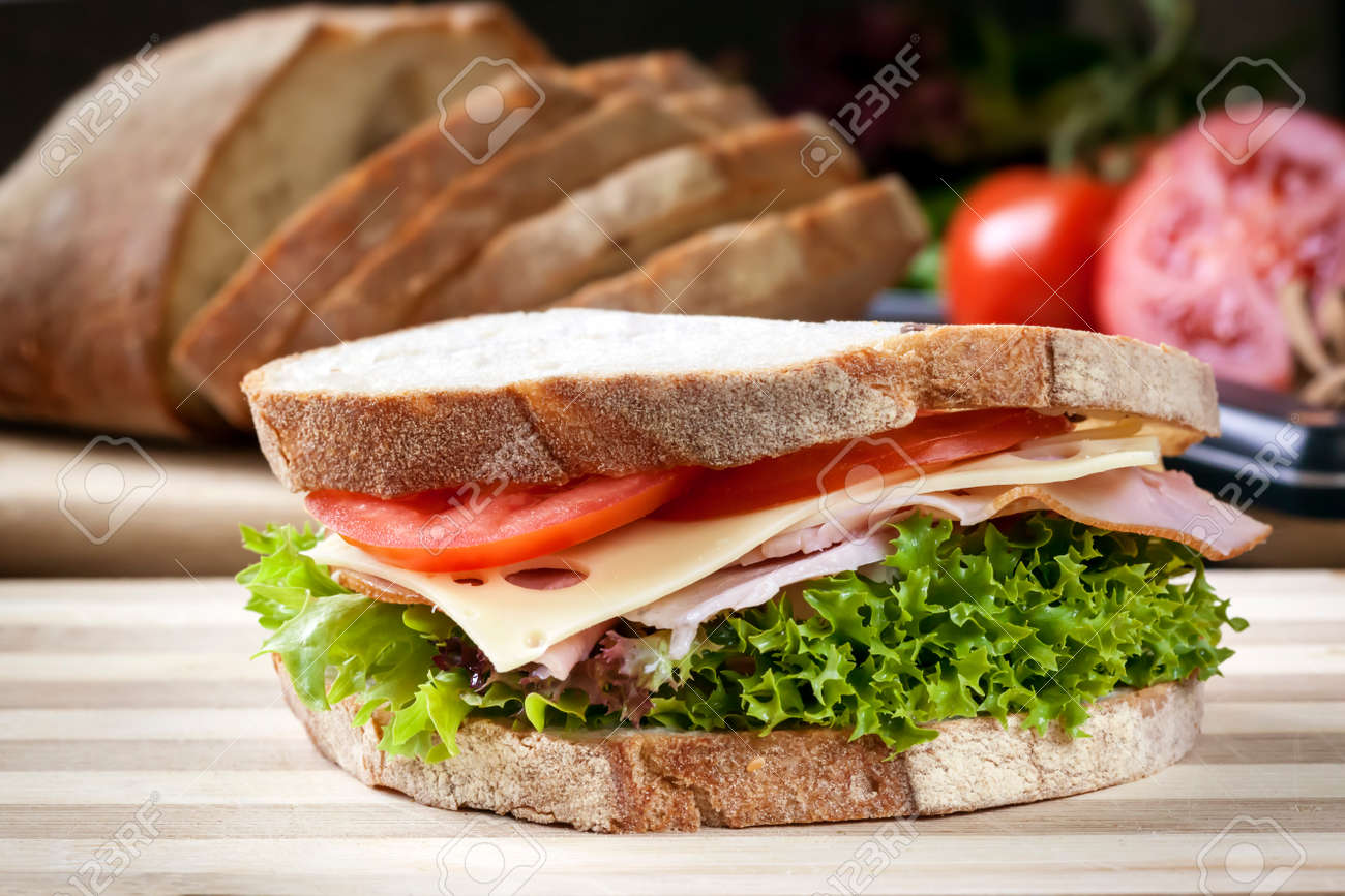 Ham sandwich with salad and cheese. Loaf of bread behind. - 50838955